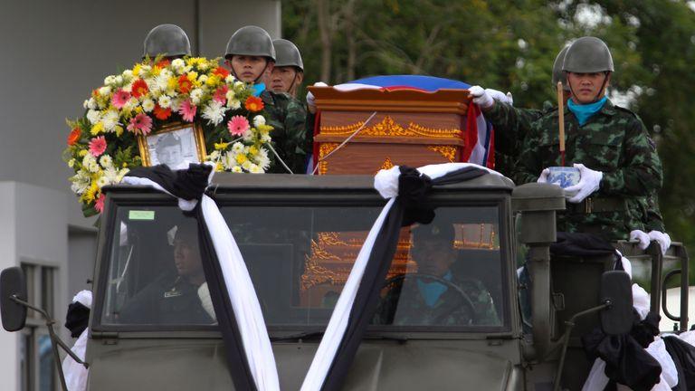 An honour guard carries the coffin of diver Saman Gunan