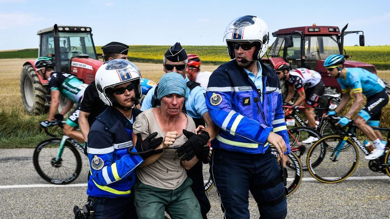 Gendarmes detain a protesting farmer as the pack rides behind during the 16th stage of the 105th edition of the Tour de France cycling race