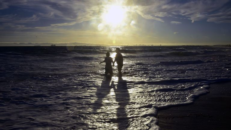 Shadows are cast as the sun nears setting and children cool off at Sunset Beach in Huntington Beach, California