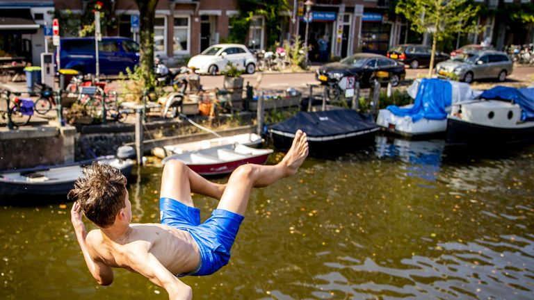 A boy jumps into a canal in Amsterdam