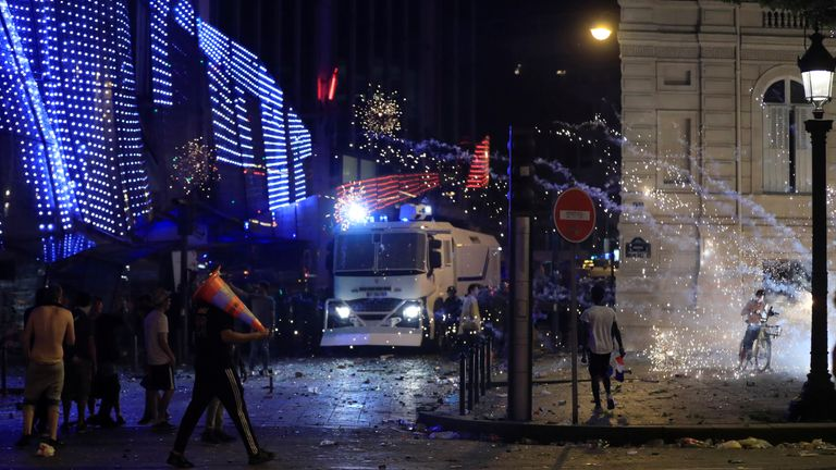 French CRS riot police advance during clashes on the Champs-Elysees after after France win the World Cup final.