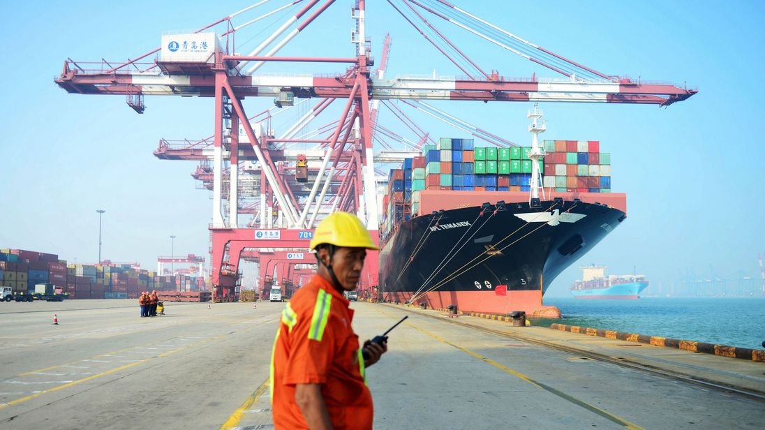 A Chinese worker looks on as a cargo ship is loaded at a port in Qingdao, eastern China's Shandong province