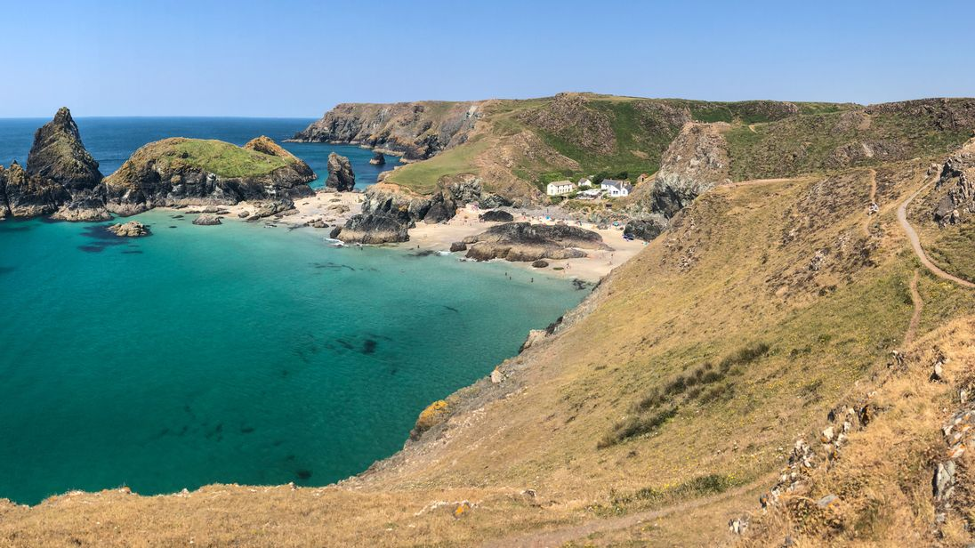 People enjoy the fine weather as they visit Kynance Cove on the Lizard Peninsula