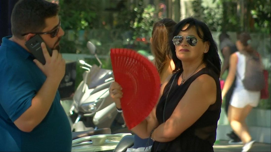 A woman fans herself as the temperatures soar above 40C
