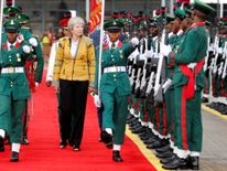 Theresa May inspects a Guard of Honour as she arrives in Abuja
