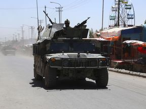 Afghan security forces patrol along a road in the city of Ghazni