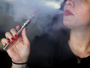 MIAMI, FL - APRIL 24:  Julia Boyle enjoys an electronic cigarette as she waits for customers at the Vapor Shark store on April 24, 2014 in Miami, Florida. Brandon Leidel, CEO, Director of Operations.Vapor Shark, said he welcomes the annoucement by the Food and Drug Administration that they are proposing the first federal regulations on electronic cigarettes, which would ban sales of the popular devices to anyone under 18 and require makers to gain FDA approval for their products.  (Photo by Joe Raedle/Getty Images)