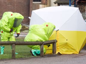 Experts in hazmat suits next to a tent covering a bench in the Maltings shopping centre in Salisbury