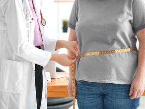 Young female doctor measuring waist of overweight woman with centimeter in clinic