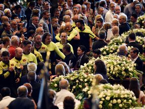 Firefighters pay their respects to the victims of the Morandi Bridge collapse
