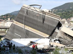 Rescue workers can be seen next to a large section of the fallen motorway