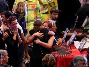 Families hug each other next to the coffins of victims of the Genoa bridge collapse
