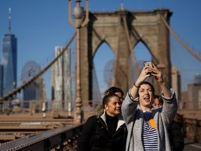 NEW YORK, NY - DECEMBER 01: A group of friends takes a photograph on the Brooklyn Bridge, December 1, 2017 in New York City. The photo-sharing app Instagram has released data for its most-Instagrammed cities and locations for 2017. New York City is ranked number one, with Moscow and London coming in second and third. Among the most photographed locations in New York City were the Brooklyn Bridge, Times Square and Central Park. (Photo by Drew Angerer/Getty Images)