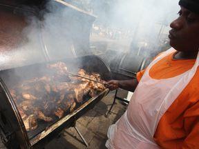 A man makes jerk chicken at Notting Hill Carnival