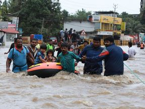 Indian volunteers and rescue personal evacuate local residents in a boat in a residential area at Aluva in Ernakulam district, in the Indian state of Kerala