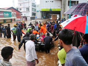 Indian navy and rescue personnel evacuate local residents in an boat at Aluva, in the Indian state of Kerala