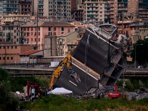 Rescuers work among the rubble of the Morandi motorway bridge