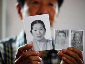 A man selected as a participant for a reunion shows pictures of his deceased mother and little brothers living in North Korea, at a hotel used as a waiting place in Sokcho, South Korea, August 19, 2018. REUTERS/Kim Hong-Ji NO RESALES. NO ARCHIVES.