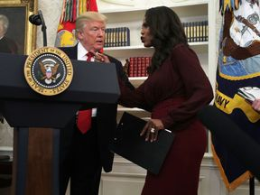 Omarosa Manigault Newman briefs Donald Trump during an event in the Oval Office