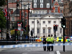 Police stand in the street after a car crashed outside the Houses of Parliament