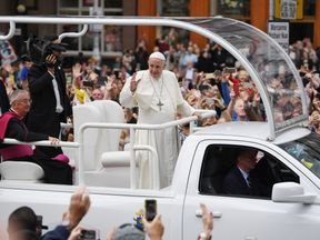 Pope Francis greets the public as he travels through Dublin in the Popemobile