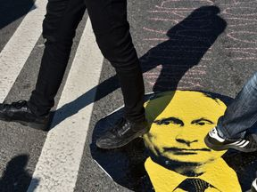 Protesters step on a sticker of Vladimir Putin during a rally against the government's proposed pension reform
