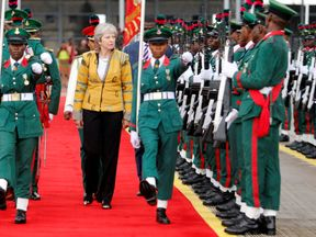 Theresa May inspects a Guard of Honour as she arrives in Abuja, Nigeria