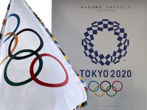 The Olympic flag (L) and the logo of the Tokyo 2020 are displayed during the official flag arrival ceremony at the Tokyo's Haneda airport on August 24, 2016. The Olympic flag arrived in Tokyo on August 24, as Japan's capital gears up to host the 2020 Games, with officials promising smooth sailing after Rio's sometimes shaky 2016 instalment. / AFP / KAZUHIRO NOGI (Photo credit should read KAZUHIRO NOGI/AFP/Getty Images)