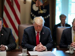 President Donald Trump prays during a cabinet meeting were they discussed sanctions
