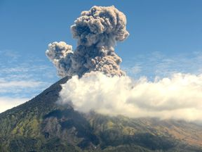 A plume of fresh ash is released as Mount Agung volcano erupts at the Kubu subdistrict in Karangasem Regency on Indonesia's resort island of Bali on July 6, 2018. (Photo by SONNY TUMBELAKA / AFP) (Photo credit should read SONNY TUMBELAKA/AFP/Getty Images)