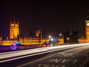 Police Cars and Ambulance on Westminster Bridge, London at Night with The Houses of Parliament and Big Ben