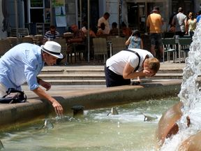 Tourists cool off at a fountain during the heatwave at the Virgin Square in Valencia, Spain