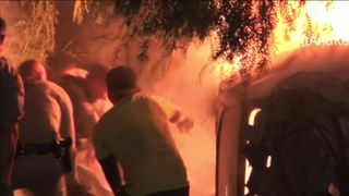 Passers-by and police rescued an unconscious man from the burning wreckage of a car crash in California.