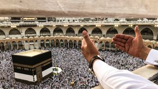 A muslim pilgrim prays while others circle the Kaaba and pray at the Grand mosque ahead of annual Haj pilgrimage in the holy city of Mecca, Saudi Arabia