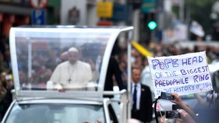 A protester holds a banner as Pope Francis drives by during his visit in Dublin, Ireland