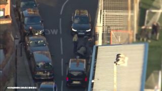 Police officers swooping in to arrest Naa'imur Zakariyah Rahman