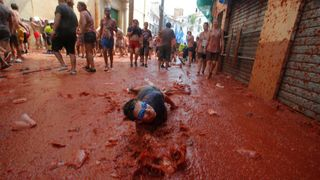 """A reveller plays with tomato pulp during the annual """"Tomatina"""" festival in Bunol, near Valencia, Spain"""