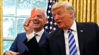 President Donald Trump holds a red card as he meets with FIFA President Gianni Infantino in the Oval Office