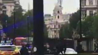 Armed police reach the scene of a crashed vehicle outside the Houses of Parliament