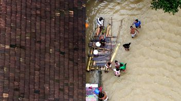 People wait for aid next to makeshift raft at a flooded area in the southern state of Kerala, India