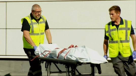 The suspect is wheeled onto an ambulance