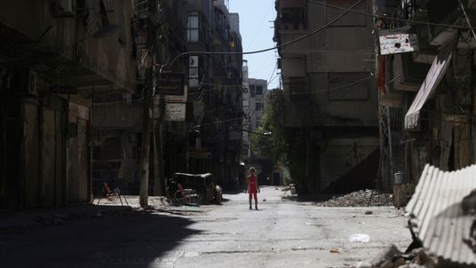 A girl stands in a damaged street in Eastern Ghouta in 2014, a year on from the chemical attacks in the area