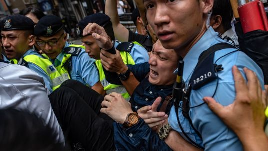 Police remove a protester from outside of the Foreign Correspondents Club  in Hong Kong