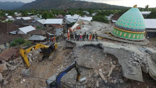 Rescuers search for survivors under the rubble of the Jamiul Jamaah mosque in north Lombok