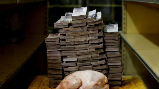 A 2.4 kg chicken is pictured next to 14,600,000 bolivars, its price and the equivalent of 2.22 USD, at a mini-market in Caracas, Venezuela