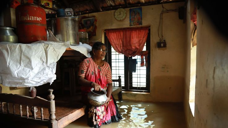 A woman sits inside her house in the Ernakulam district of Kochi
