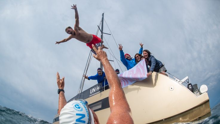 Lewis' crew celebrated passing halfway with a banner and a song while 1st mate, Rowan, jumped in. Pic: Lewis Pugh