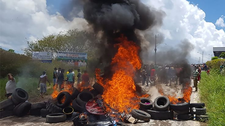 Residents of the Brazilian border town of Pacaraima burn tyres and belongings of Venezuelans immigrants after attacking their two main makeshift camps