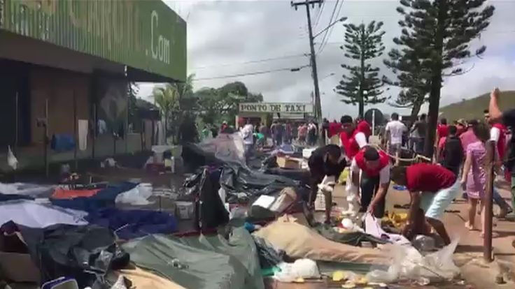 Residents of the Brazilian border town of Pacaraima destroying belongings of Venezuelans immigrants during an attack at their two main makeshift camps