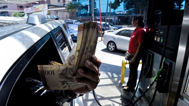 A customer shows Bolivar bills while at a gas station in Caracas where people queuing for petrol